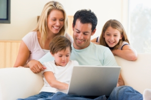Family in living room with laptop smiling