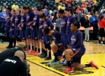 Phoenix Mercury's Kelsey Bone, right, and Mistie Bass, second from right, kneel during the playing of the national anthem before the start of a first round WNBA playoff basketball game against the Indiana Fever, Wednesday, Sept. 21, 2016, in Indianapolis. (AP Photo/Darron Cummings) ORG XMIT: NAF101